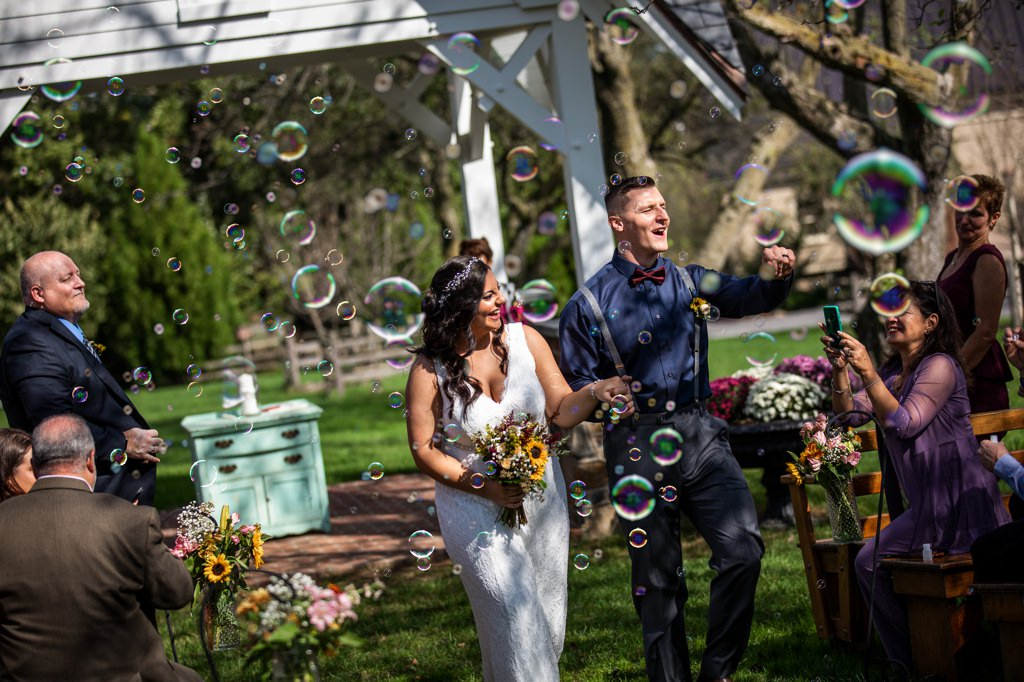 bride and groom walking throught bubbles at ironstone ranch wedding