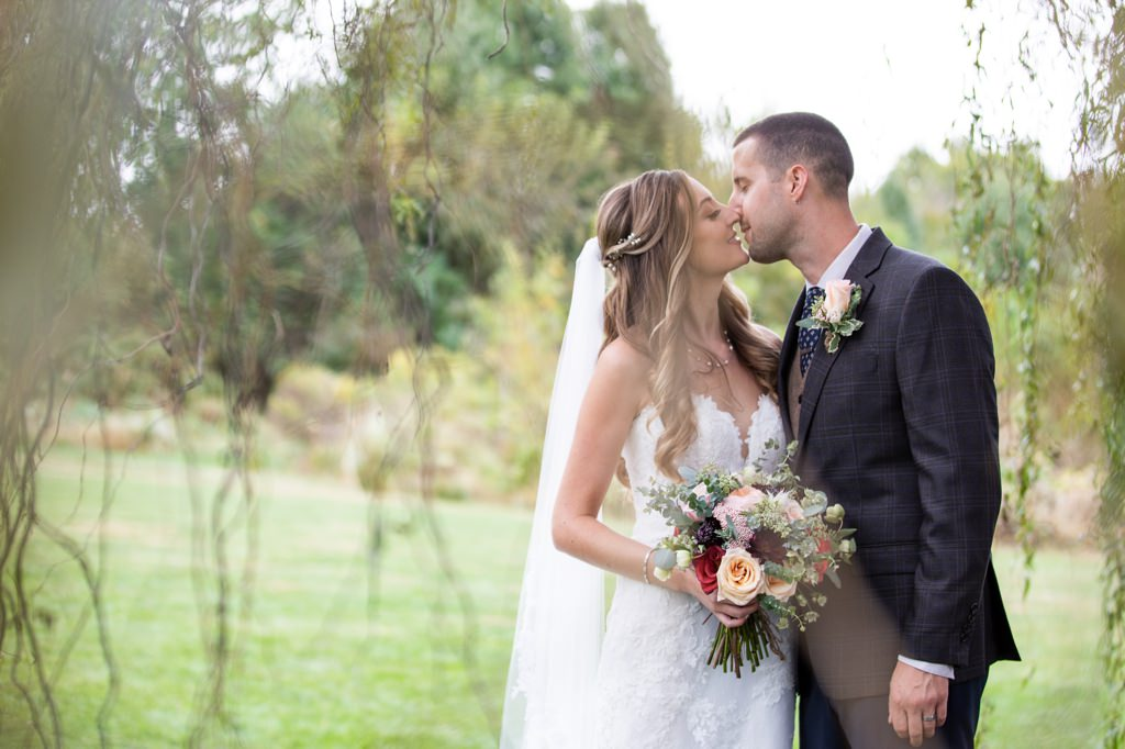 bride-groom-kissing-under-willow-tree-barn-at-silverstone